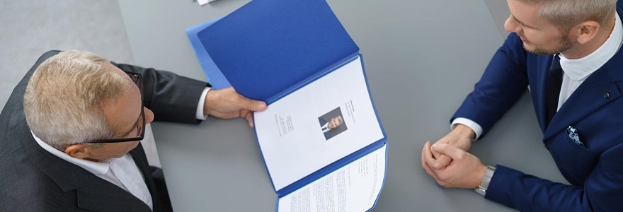 interviewer looking at document in blue folder with man in interview