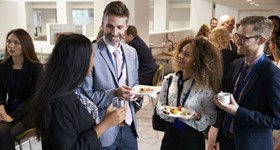A group of professionals having a conversation with some snacks at a networking event