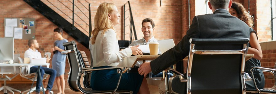 Group of people in an office chatting and laughing