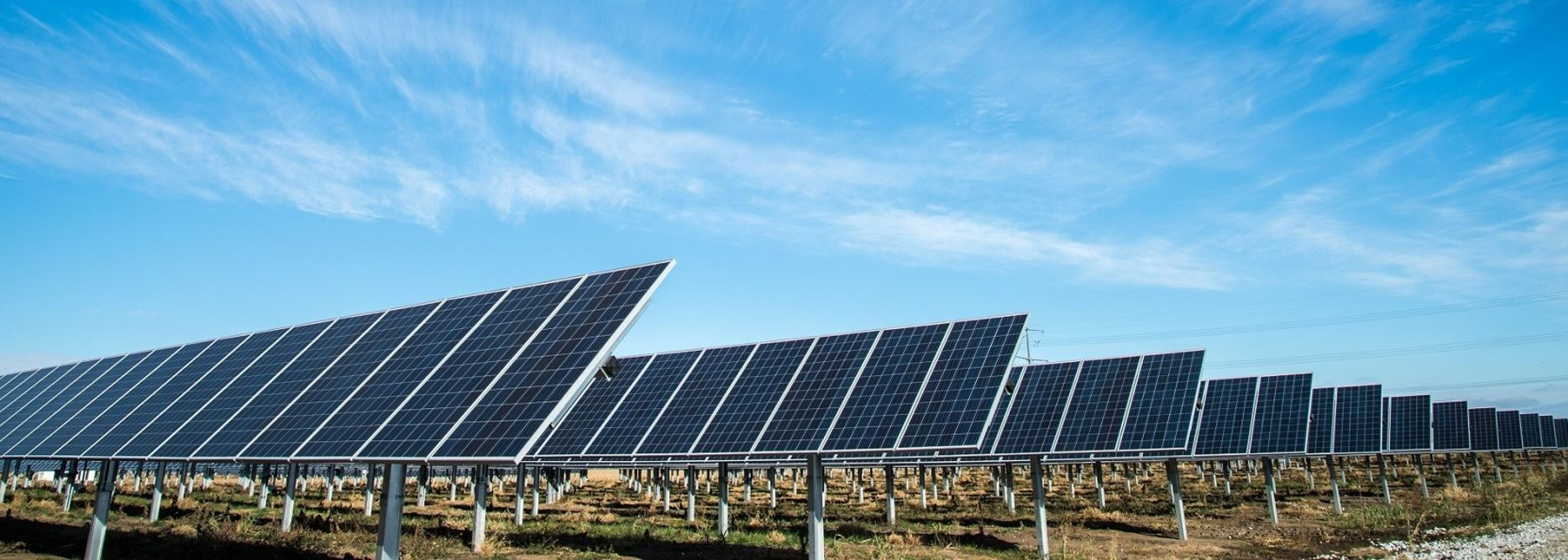 large angled solar power panels in field with slightly cloudy blue skies